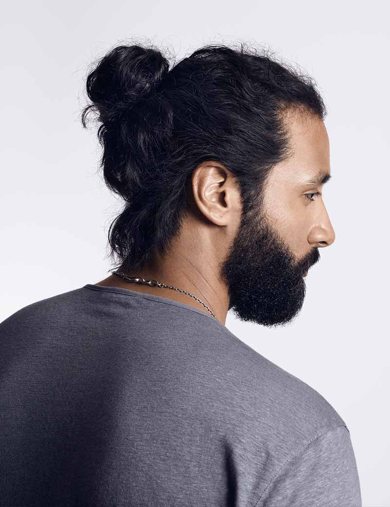 man with man bun hairstyle using redken brews work hard