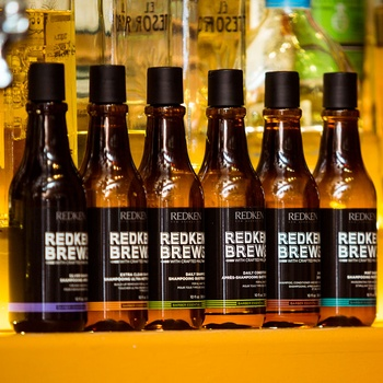 A lineup of Redken Brews shampoos on an orange counter.