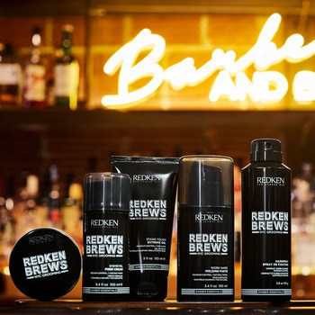Redken Brews styling products in black bottles on a bar counter.