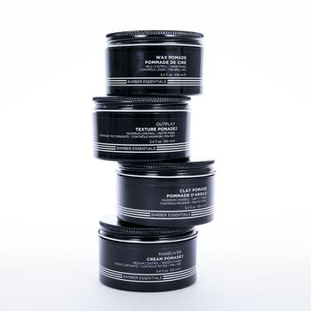 Four Redken Brews Pomade jars stacked on top of each other in front of a white background.