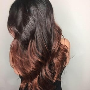 Dark brown roots and rose gold haircolor ends.