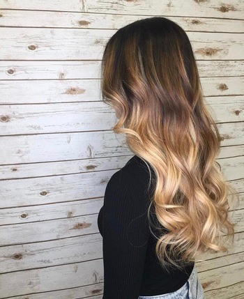 Curly champagne blonde ombré hair and dark brown roots.