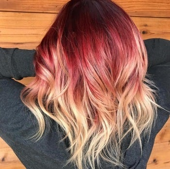 Curly red ombré roots and blonde haircolor ends.