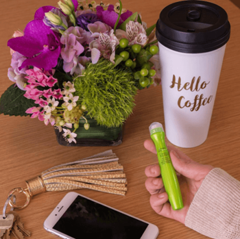 Model holds eye cream next to coffee mug, flowers and cell phone