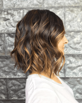 Model with brunette hair and warm caramel balayage.