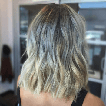 Model with blonde hair, dark roots and grey balayage.