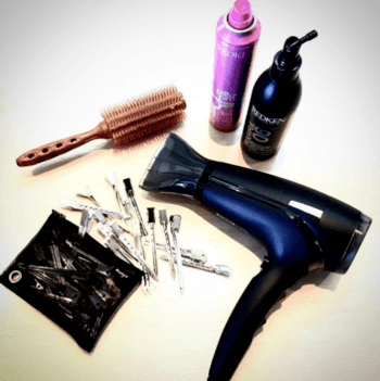 A look at a hairstylist's must-haves including a hair dryer, bobby pins, a brush, and styling products.