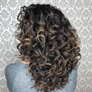 Model with brunette hair and tight curls