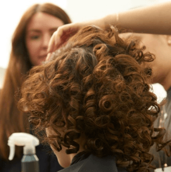 Model backstage at fashion week with large curls