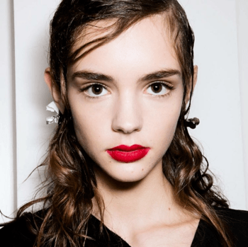 Model backstage at fashion week with wet hair and bright red lip