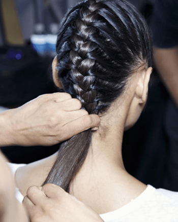 Model with braided hairstyle is having her hair styled backstage at Fashion Week.
