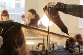 Redken stylist blow drying model's hair