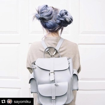 : Model with purple hair, messy buns and grey backpack