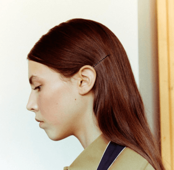 : Model with sleek auburn hair and bobby pin style