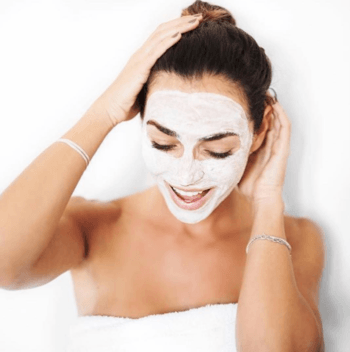 Brunette model with clay face mask and topknot hairstyle