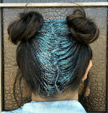 Two high messy buns on brunette model with teal glitter roots.