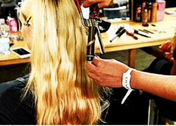 Stylist curling model's hair backstage at fashion week.