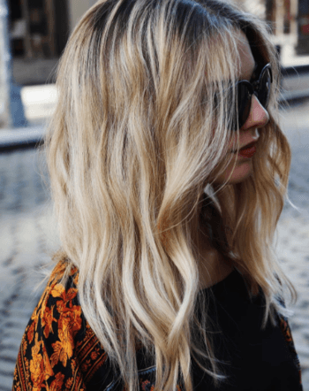 Blond model with loose waves and black sunglasses.