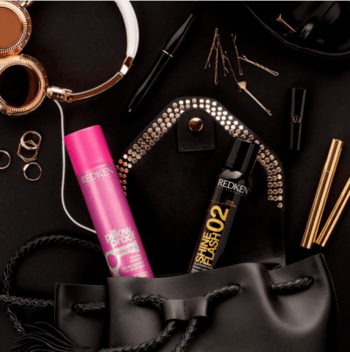 Overview of purse filled with dry shampoo, shine spray, and other accessories.