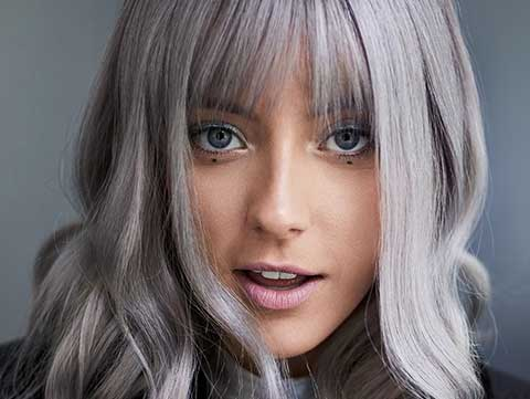 Redken Muse Chloe Norgaard in curled icy blonde hair with bangs created by Redken Artist Sean Godard.
