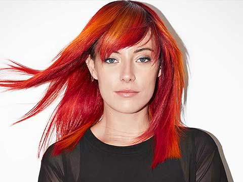 Redken Muse Chloe Norgaard wears fiery red orange haircolor created by Redken Artist Sean Godard.