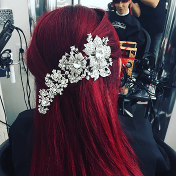 Model with bright red hair and bold silver and white hair accessory.