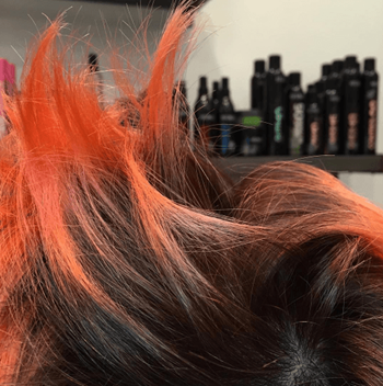 Close-up image of model with black and orange hair