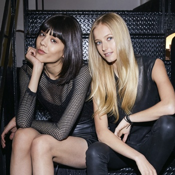 Blonde model and model with black hair sit on steps wearing all black clothing