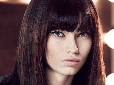 Model with shiny brunette hair and blunt bangs.