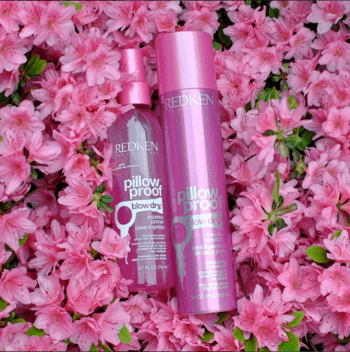 Image of dry shampoo and blow dry primer spray over pink flowers