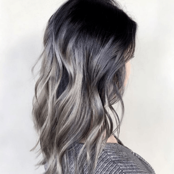 Model with metallic grey ombre hair color and loose curls