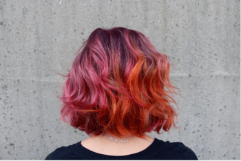 Bold pink and orange hair color created by stylist, Reavey Dalfonsi