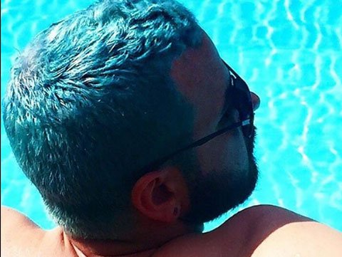 Man with blue hair lounging in pool.