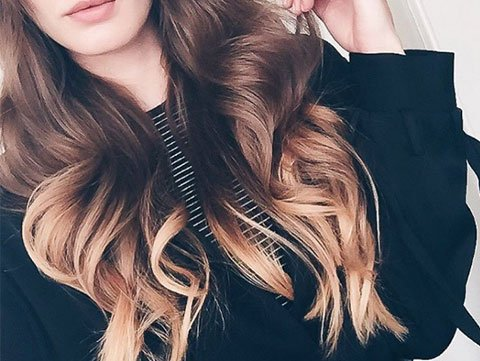Model with brunette and gold ombre hair color and loose waves