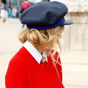 Blonde French woman wearing red sweater and navy hat.