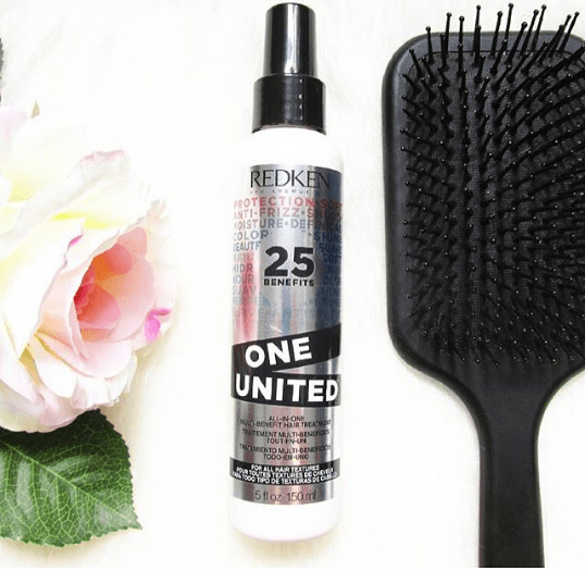 Leave-in conditioner on white background with black paddle hairbrush and flower