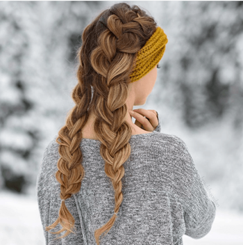 Woman with blonde balayage and grey sweater wears a double dutch braid hairstyle in winter.