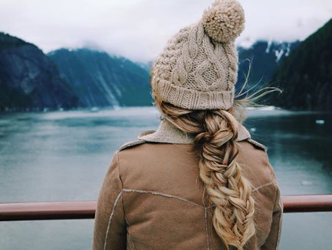 Blonde woman in winter coat and beige beanie stands at the edge of a lake in winter.
