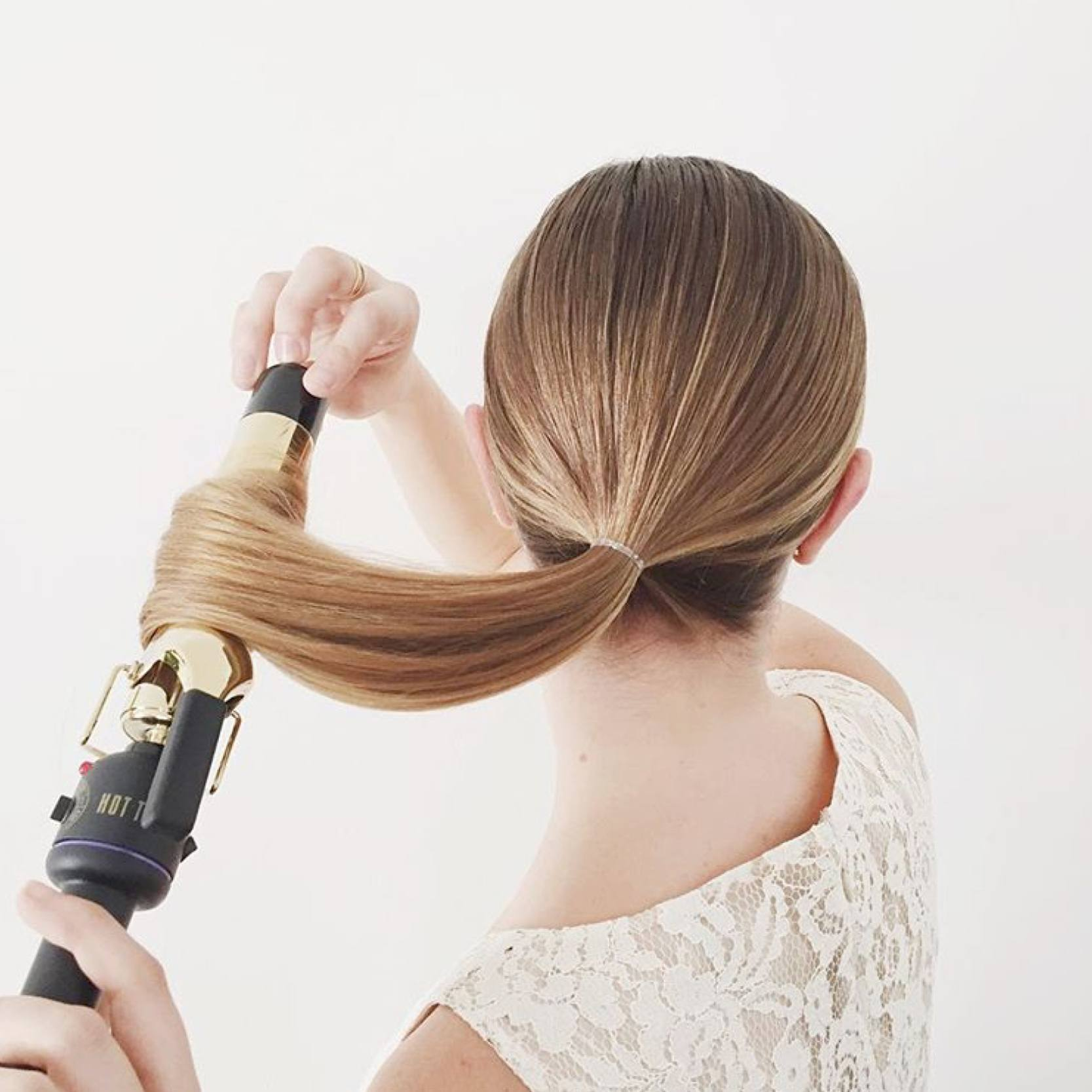 Model curls her hair away from her face using a curling iron.
