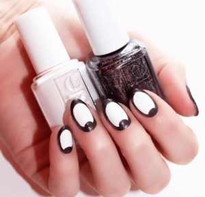 Model displaying black and white nail art with matching nail polish bottles.