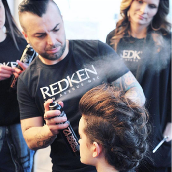Redken artist sprays hairspray to set a model's hairstyle.