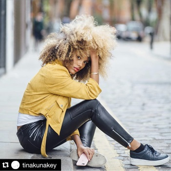 Model with blonde, spiral curls, yellow jacket and leather pants poses on sidewalk.